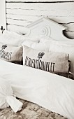 Detail of bed with bolsters, pillows and carved wooden headboard painted white
