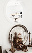 Buddha figurine flanked by candlesticks in front of silver tray leaning against wall below porthole aperture