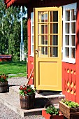 Half-open front door in ornate facade of Swedish wooden house painted red and yellow