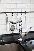 Retro tap fittings on undermount sink and kitchen utensils hanging from metal rail