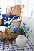 Blue cushion on wicker chair and vase of delphiniums on blue and white, patterned, tiled floor