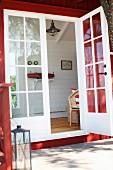 Blick von aussen durch die Fenstertür eines roten Holzhauses in Wohnraum