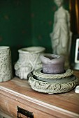 Purple pillar candle in ornate stone candle holder