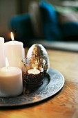 White, lit candles and tealight holder on pewter tray