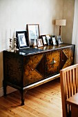 Collection of framed photos on Biedermeier-style, antique sideboard in corner