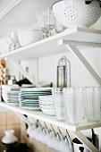 Glasses and crockery on white bracket shelves