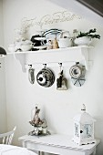 Cake tins hanging from bracket shelf above vintage lantern on console table