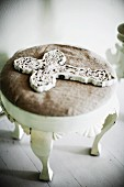 Ornate, white, vintage cross on footstool with cushion