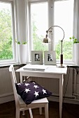 Small work area below window with white-painted chair and table and retro table lamp