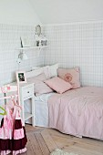 Nostalgic, girl's bedroom; single bed with pink bed linen in corner and pastel tartan wallpaper