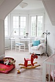 Child's bedroom with rocking horse, toy box, wooden floor and armchair and table in window bay