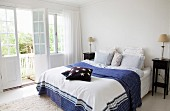 Double bed with blue and white patterned bed cover and dark wood bedside cabinet in bedroom