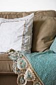 White cushion with trim on ecru sofa