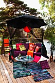 Colourful relaxation area on terrace below black parasol with red lantern and view of trees and lake
