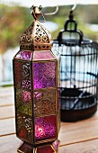 Bronze-coloured, Oriental-style metal lantern with coloured glass panels on wooden terrace