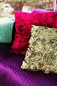 Silk-effect, gold cushion with pattern of roses and red plush cushion on purple couch