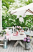 Festively set table and various seats below parasol decorated with white lanterns on romantic wooden terrace; white lilac in background