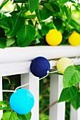 Lampiongirlande mit farbigen Kugel- Lampenschirmchen an weißem Geländer und Blättern im Garten