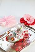 Weihnachtsbaumanhänger auf Silbertablett; daneben selbstgebastelte Papierblumen