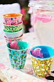 Colourful melamine beakers and flamingo-shaped plastic ice cubes for garden party