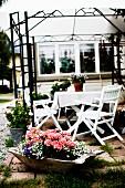 Terrassenplatz mit weiss lackierten Holzstühlen um Tisch, unter Rankgerüst als Pavillon, davor Holzschale mit Blumen auf Boden