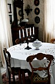 Chairs with carved backrests around round table with white tablecloth in corner of traditional interior
