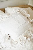 Initials embroidered on cushion with white cover and ruffles