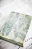 Antiquarian book with initial on cover on white lace tablecloth