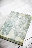 Antiquarisches Buch mit Initiale auf weisser Spitzendecke