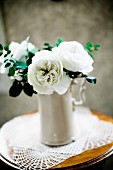 White roses in china jug on side table with lace doily
