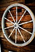 Altes Rad mit gedrechselten Speichen an Holzwand aufgehängt