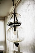 Pendant lamp with spherical glass lampshade hanging from chain