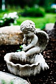 Stone bird bath with cherub figurine outside