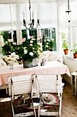Verwitterte Holz Klappstühle weiss lackiert, vor Tisch mit Blumentopf & Tischdecke in Loggia-Ecke
