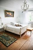 Schlichtes Schlafzimmer mit Doppelbett und Nachttisch, weiss lackiert im Regency Stil, Kronleuchter mit Glasschmuck