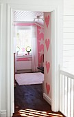 View into pink, child's bedroom with heart and star patterns on walls