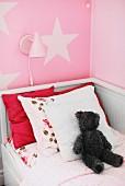 Weisses Kinderbett aus Holz mit Kissen und Teddybär, Wandleuchte auf rosa Wand mit Sternmotiv