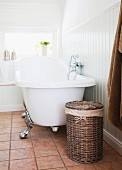 Laundry basket and free-standing, vintage clawfoot bathtub against wainscoting in white bathroom