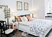 Double bed with collection of scatter cushions against upholstered headboard and table lamps on white bedside tables in rustic bedroom