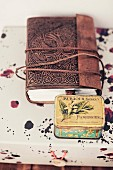 Book with antique leather cover and vintage tin on surface with pattern of splashes