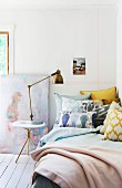 Stack of pillows on bed, retro brass table lamp on side table and pattern of pastel washi tape stripes on wall