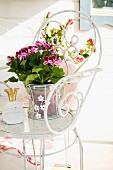Angel pelargonium in wire planter on romantic metal chair