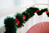 Artificial fir garland and red ribbon wrapped around balustrade and backrest of red and white striped armchair