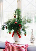 Red Christmas baubles hanging from pine branches in vase and china gnome on windowsill