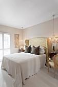 Elegantes Schlafzimmer, weisse Tagesdecke auf Doppelbett, mit hohem, gepolstertem Kopfteil mit glänzendem Bezug, seitlich Kronleuchter