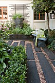 Flooring made from dark wooden sleepers and gravel in courtyard with planters and trellising on house facade