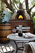 Wine glasses and carafe on bistro table in front of blazing fire in masonry pizza oven
