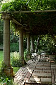 Charming seating area under climber-covered pergola with antique stone pillars