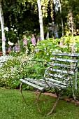 Old, battered garden armchair in front of flowering foxgloves in flowerbed