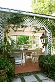 White wicker chairs and wooden table on roofed, country-style terrace surrounded by lattice trellising with terracotta floor tiles
